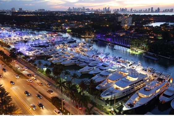 superyachts line up alongside Collins Avenue for the Miami Yacht Show at night