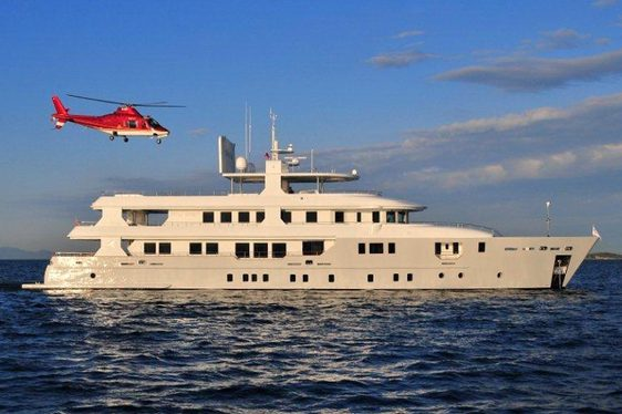 Side profile of charter yacht 'Lady Katarina' witb a helicopter about to land on her helideck