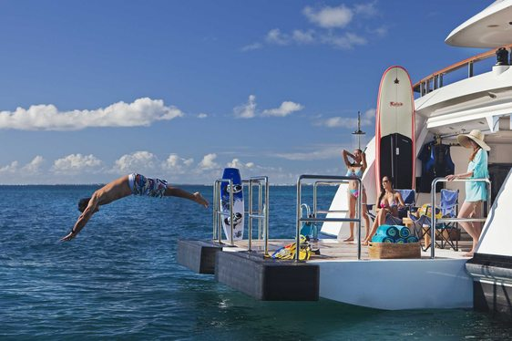 charter guests relax on the swim platform aboard superyacht JAGUAR
