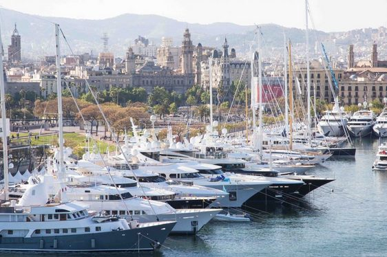 yachts line up in OneOcean Port Vell for the MYBA Charter Show with Barcelona skyline in the background