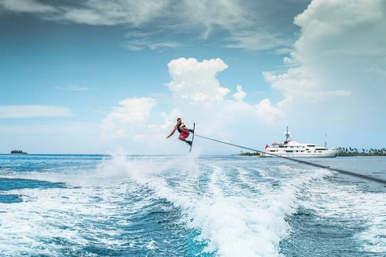 charter guest on flyboard with superyacht CALYPSO in background in Tahiti