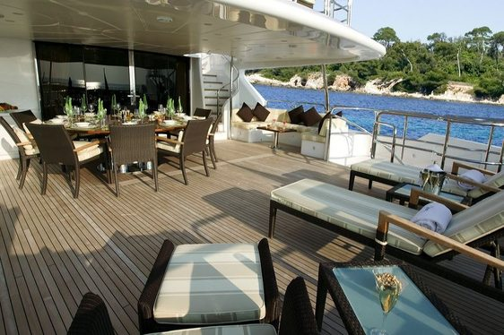 Bridge deck with sun loungers and dining table on board superyacht Mamma Mia