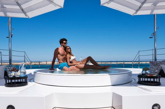 charter guests relax on edge of spa pool on the foredeck of motor yacht 11/11