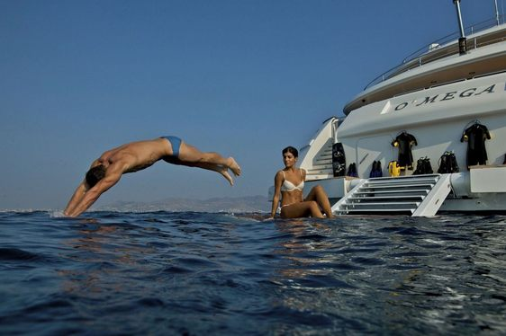 A guest dives off the swim platform of superyacht O'MEGA as a woman watches on
