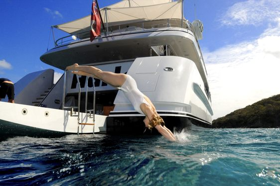 charter guest on board superyacht HARLE dives off the drop-down swim platform
