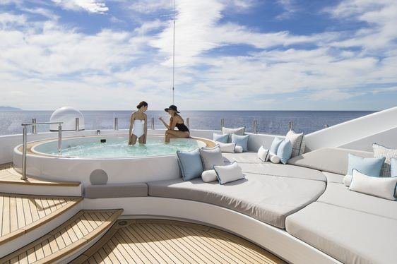 Charter guests relaxing in spa pool on sun deck of superyacht Turquoise