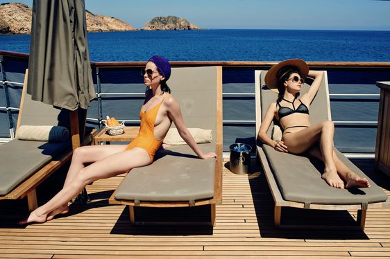 two charter guests lay back and relax on sun loungers on the sundeck of luxury yacht MENORCA