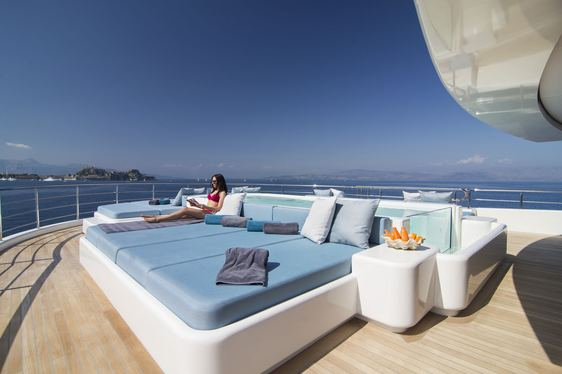 charter guest relaxes on the sun pad next to the pool on board superyacht O'PTASIA