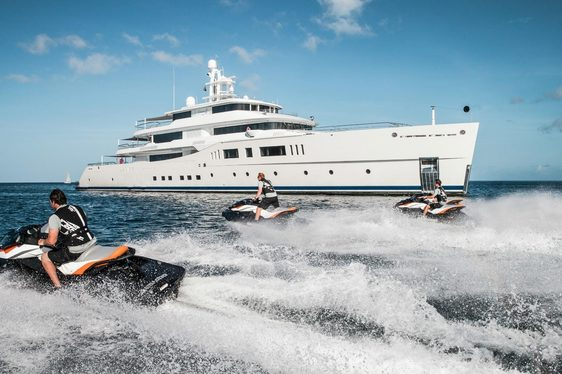 motor yacht grace e at anchor in the ocean as jet-ski's race by