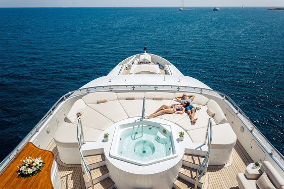 charter guests unwind on the sun pads next to the Jacuzzi on sundeck of superyacht ELENI
