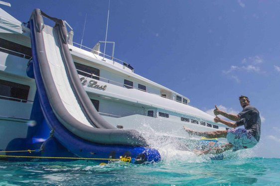 happy man gives thumbs up as he goes down slide of luxury charter yacht at last from heesen