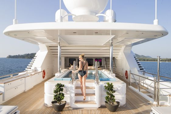 Charter Guest stepping into Jacuzzi on sun deck of superyacht Titania