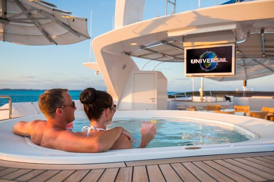 charter guests unwind in the Jacuzzi while watching a movie on the sundeck of superyacht CHECKMATE