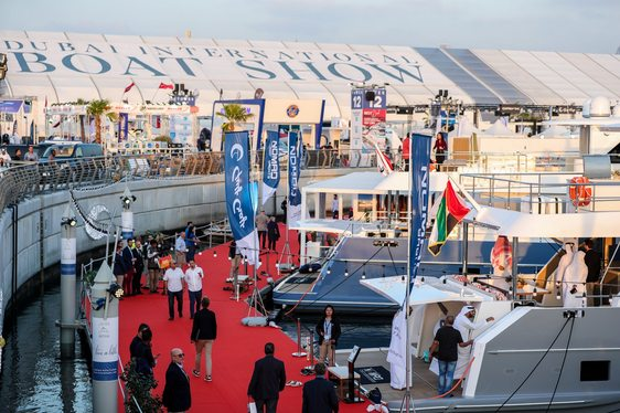 Superyachts on display at Dubai International Boat Show 2019, with people on the boardwalks and signage in background