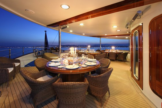 A table and a collection of chairs on the alfresco dining area of superyacht SHERAKHAN