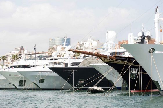 sterns of superyachts lined up in the OneOcean Port Vell in Barcelona for the MYBA Charter Show