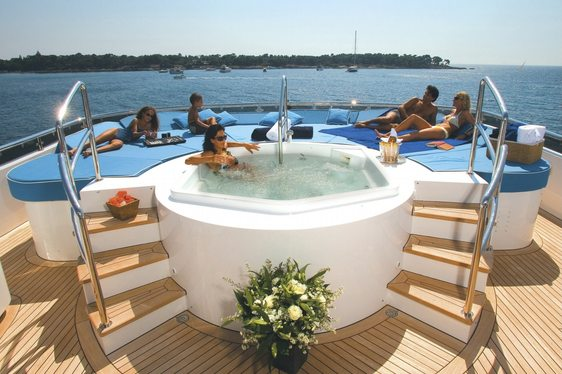 People reaxing near jacuzzi on charter yacht