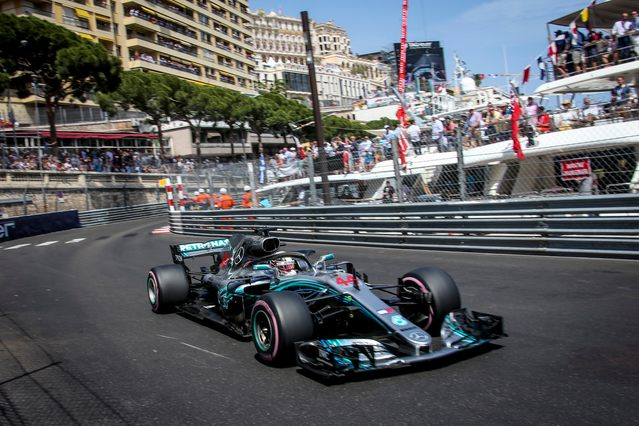 racing car powers past the superyachts lined up in Port Hercules during the Monaco Grand Prix