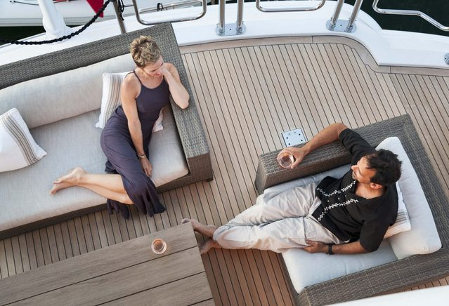 charter guests enjoy a drink together on the deck of luxury yacht Far From It