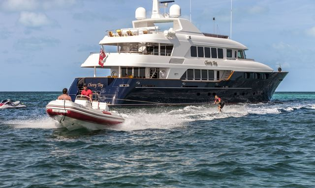 Superyacht Bacchus cruising on charter alongside tender and water skis and tender