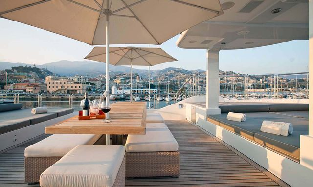 Glasses of red wine on dining table on sun deck of superyacht Sensei in port