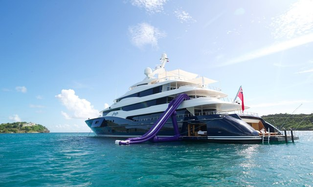 A superyacht at-anchor with an inflatable slide extending into the water