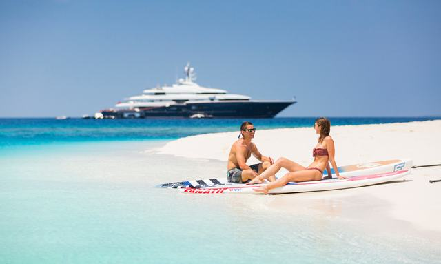 Charter guests sitting on Maldives beach Nirvana yacht in background