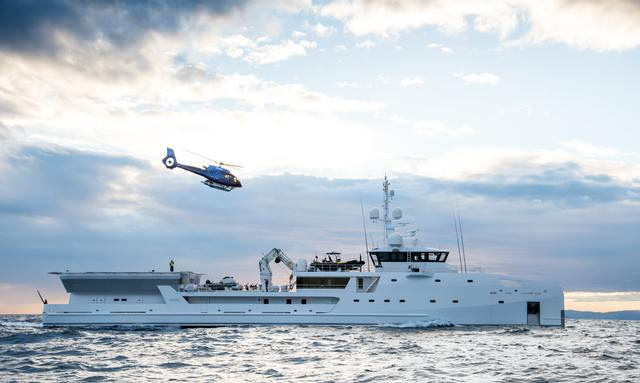 Game Changer superyacht on water with helicopter above and dark clouds behind