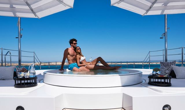 charter guests relax by the Jacuzzi on the owner's deck of superyacht 11.11