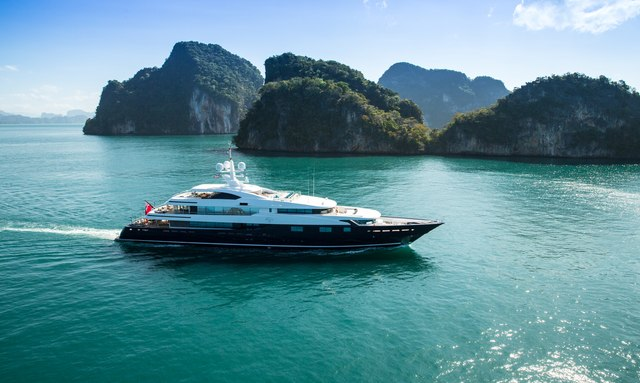 A superyacht cruises against an Indonesian backdrop