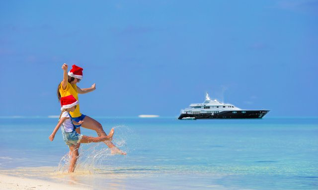Woman and child on Caribbean beach with Odessa yacht in backgound