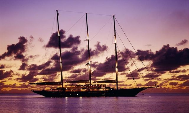 Beautiful purple sun set behind sailing yacht Athena cruising on charter