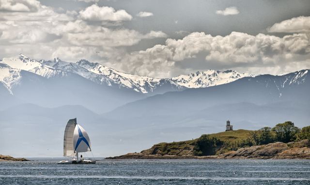 Sailing yacht in waters of San Juan Islands with snow-capped mountains in background