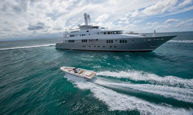 Superyacht Dream on charter at anchor with tender cruising past