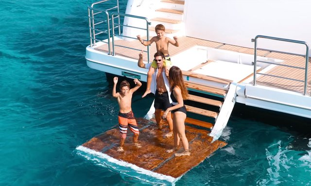 Superyacht ONEWORLD swim platform with people on board having fun