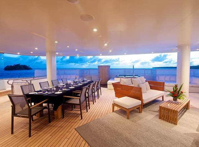 dining and seating area on deck of expedition yacht SENSES at sunset