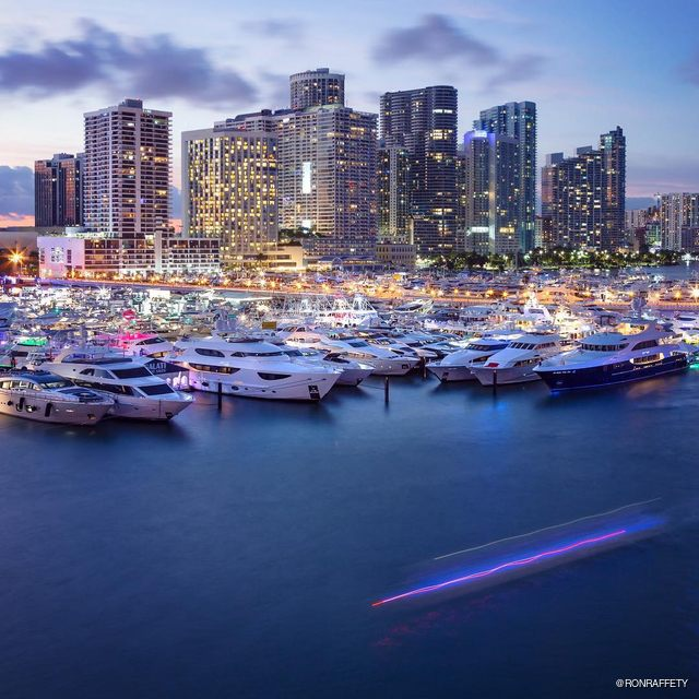 Yachts lined up for the Miami Yacht Show at night at One Herald Plaza