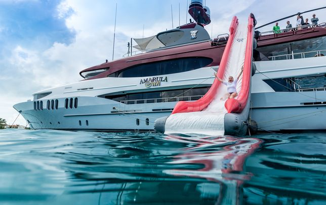 guest tries out the inflatable water slide attached to the sundeck of motor yacht Amarula Sun
