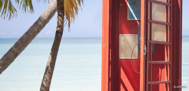 Open red telephone box on the beach