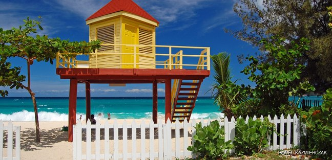 Fenced red and yellow lifeguard booth on the beach