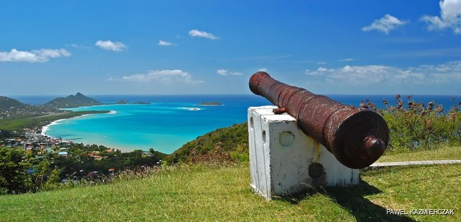 Old cannon and coastal landscape in the background