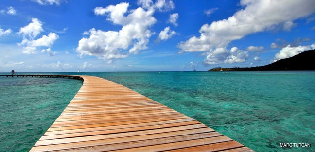 Wooden jetty and beautiful white cumulus clouds in the sky