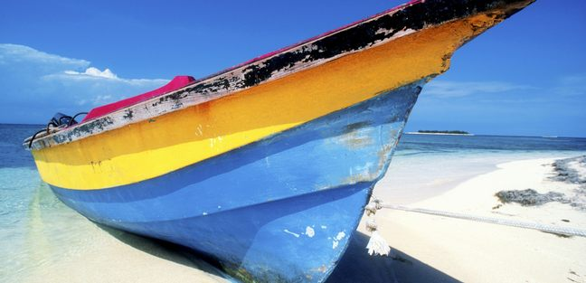 Yellow and blue boat on a sandy beach