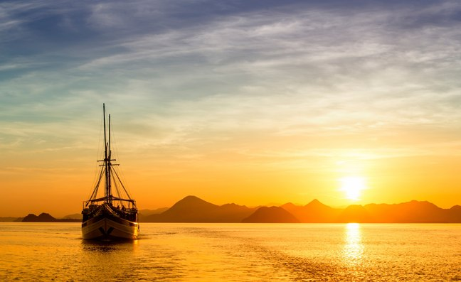 Charter yacht cruising the waters of Komodo as the sun sets
