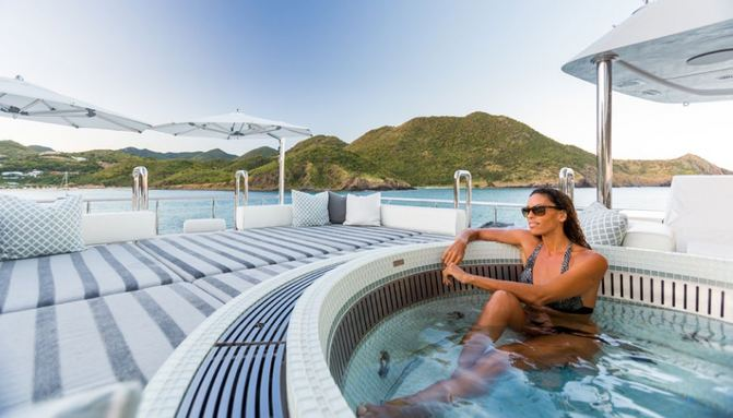 charter guest takes a dip in the Jacuzzi on the sundeck of motor yacht King Baby