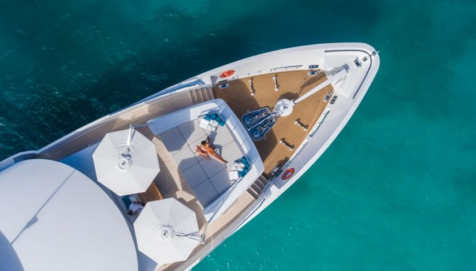 charter guest relaxes on the foredeck sun pads on board superyacht 'King Baby'