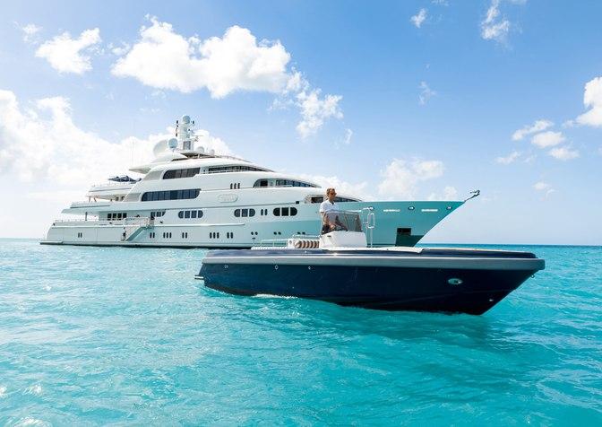 motor yacht TITANIA cruising on a charter vacation alongside the tender