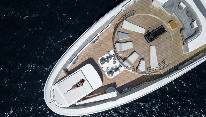 charter guest relaxes on a sunpad on the foredeck of superyacht MYSKY