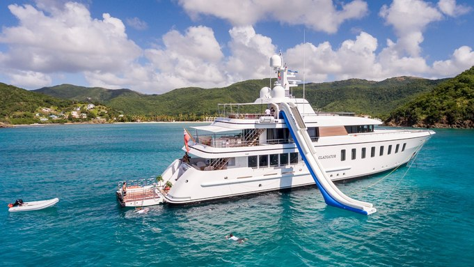 inflatable water slide drops down from the sundeck of motor yacht GLADIATOR when anchored on a yacht charter