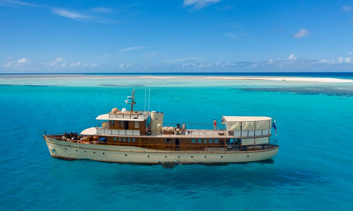 luxury charter yacht over the rainbow at sea, with sandbar in background and woman standing on sun deck looking at the bright blue sea